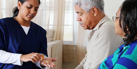 nurse giving medicine to a senior man