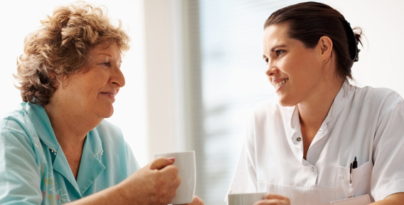 senior woman holding a cup while talking to nurse
