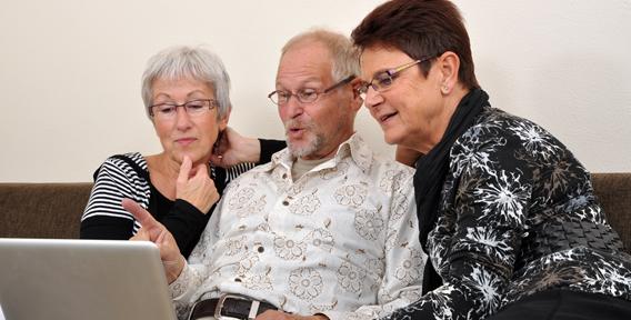 three senior's watching in the laptop