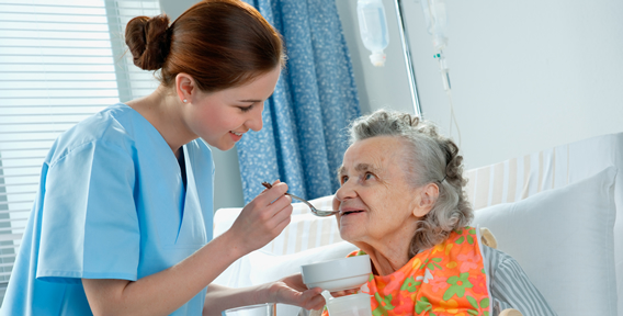 young woman helping senior woman to eat